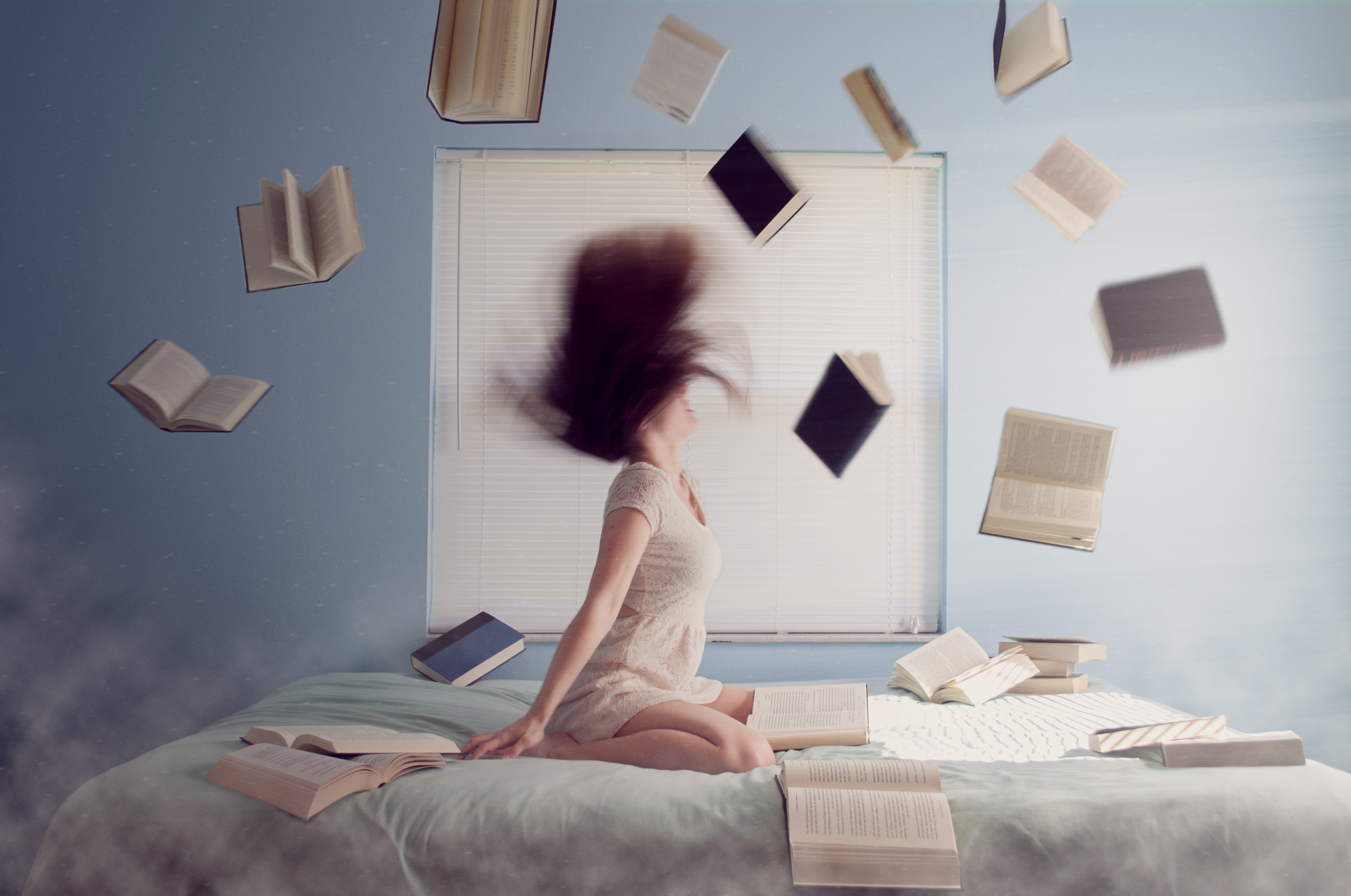 Woman sitting on a bed shaking her head backwards while books are flying around her